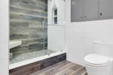 a minimalist bathroom with white tiles and wood look tiles in the shower and on the floor for a warm and soft feel
