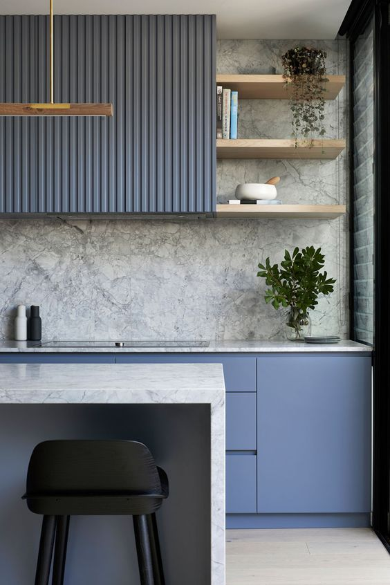 a minimalist blue kitchen with a grey stone backsplash and countertops plus potted greenery and touches of gold