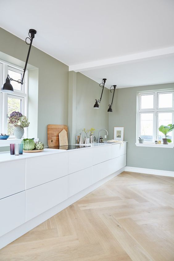 a minimalist kitchen with pale green walls, white sleek cabinets, black ceiling lamps looks fresh and natural
