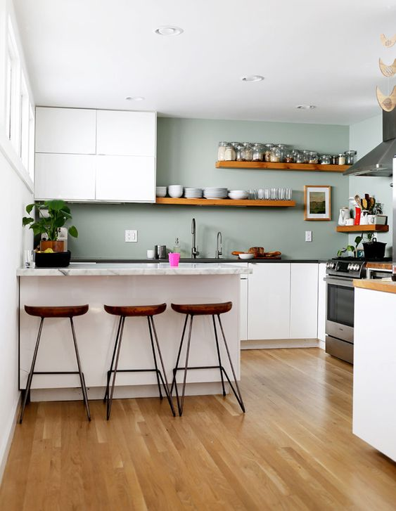a minimalist kitchen with white cabinets, pale green walls, stone countertops and wooden shelves and stools