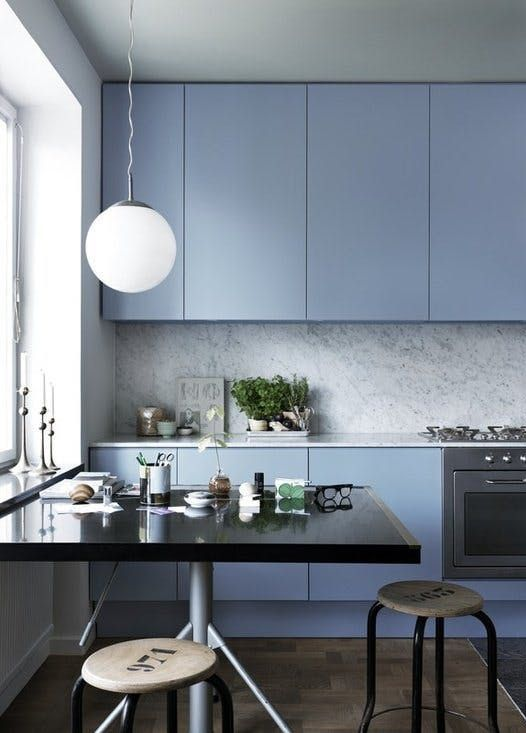 a minimalist light blue kitchen with a grey stone backsplash and countertops finished with industrial stools and a black table
