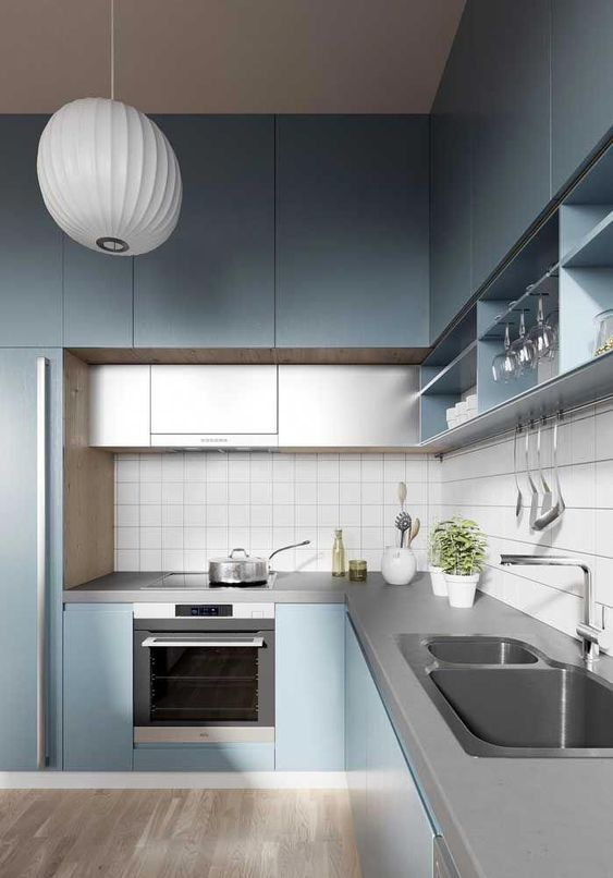 a minimalist light blue kitchen with grey additional cabinets and a concrete countertop plus a white tile backsplash