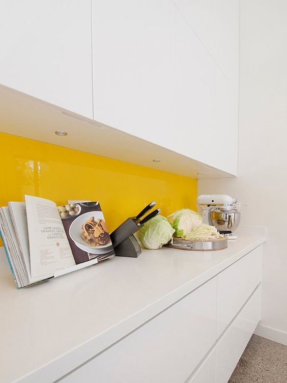 a minimalist white ktichen with a bright yellow backsplash of glass is super cool and extra bold