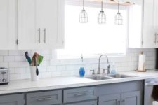 a modern farmhouse kitchen with upper white cabinets, lower grey ones, pendant lamps and metallic touches here and there