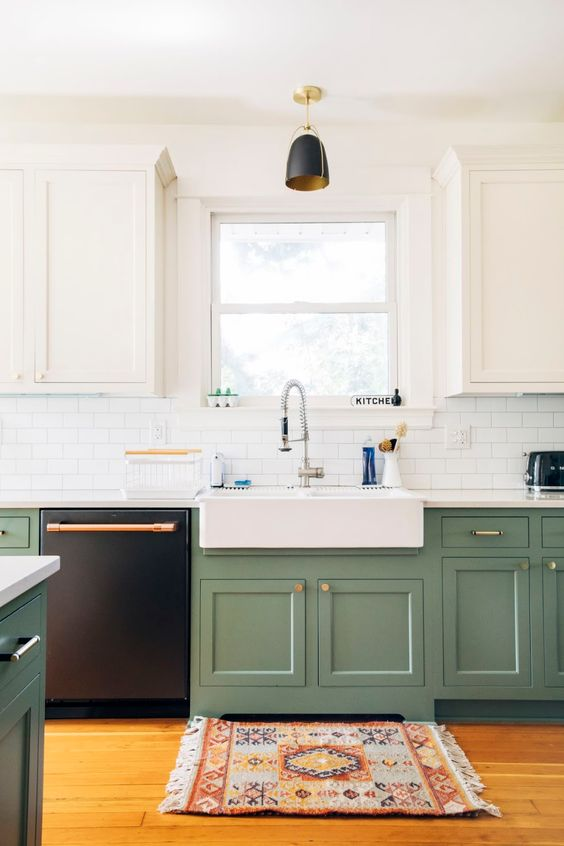 a modern kitchen with white and grene cabinets, touches of gold and copper and a boho printed rug