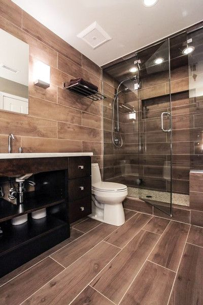 a modern rustic bathroom all clad with wood look tiles, with a dark vanity and shiny fixtures for a brighter look