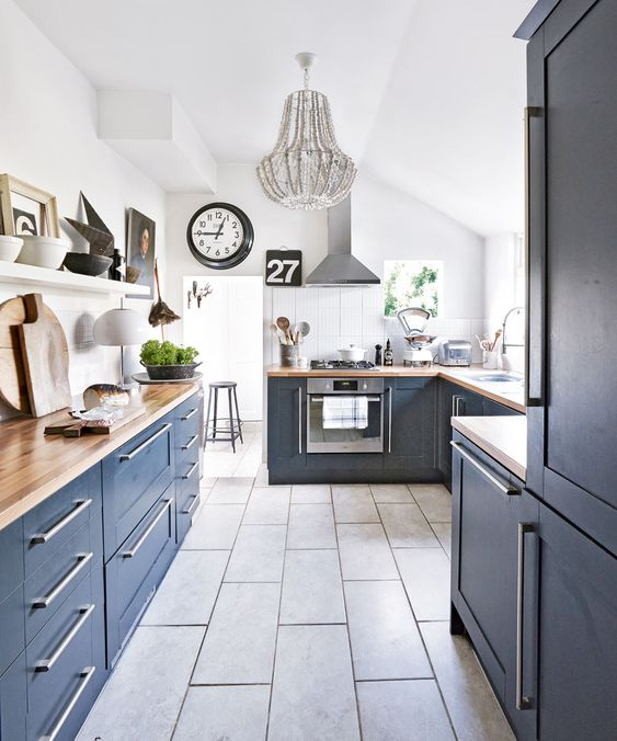 a navy kitchen with butcherblock countertops, a grey tile floor and a grey beaded chandelier for a bold touch
