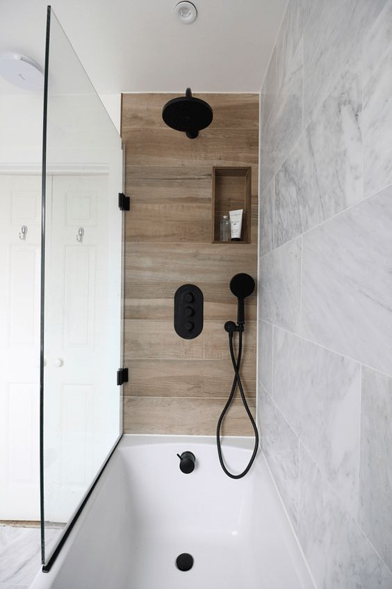 a neutral marble bathroom and a small wood look tile accent in the bathing space plus black fixtures