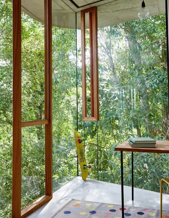 a perfect biophilic home office with glazed walls that allow natural light and a cool woodland view at the same time
