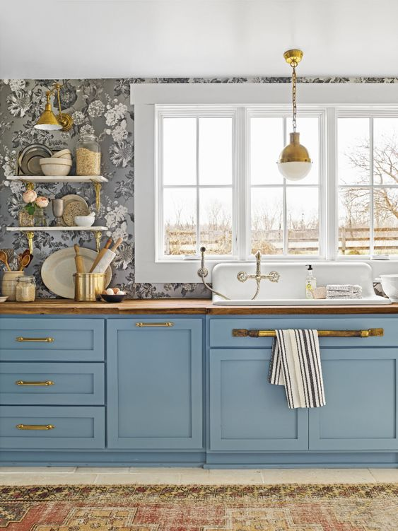 a pretty blue kitchen with a grey floral wallpaper wall and touches of gold and stained wood is vintage chic