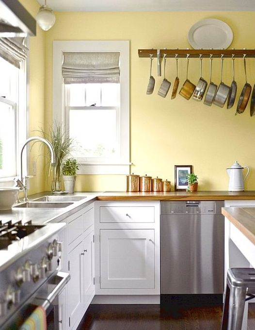 a retro kitchen with a lemon yellow wall, white cabinets, metal appliances and copper touches