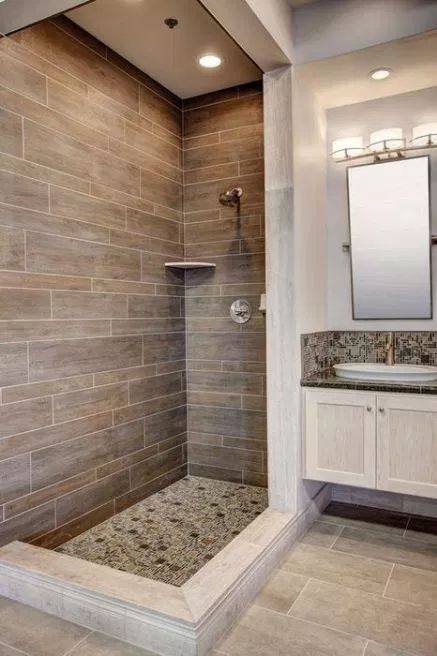 a rustic bathroom with wood look tiles, neutral ones on the floor and mosaic tiles for accents here and there