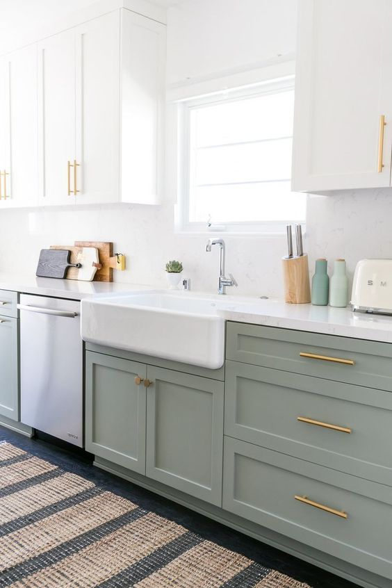 a seafoam green and white kitchen design with gold and brass hardware, with white countertops and printed rugs all over the kitchen
