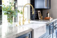 a stunning traditional kitchne in blue, with white stone countertops, a black tile backsplash and gold touches