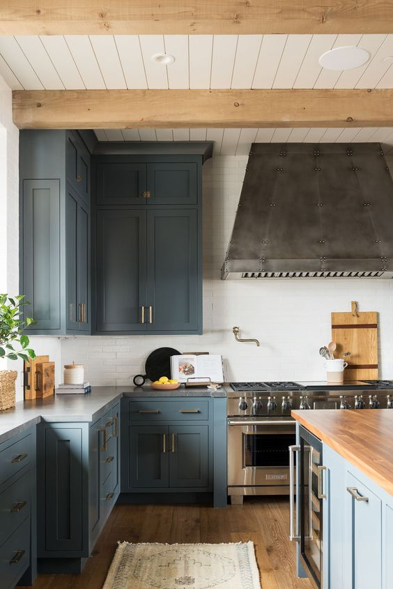 a stylish blue kitchen with stainless steel appliances, touches of natural wood and brass is a super chic and cool space