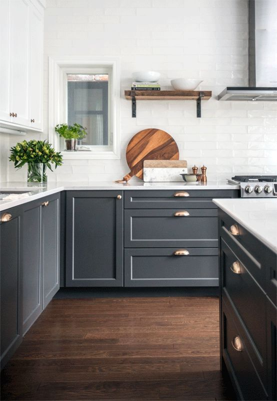 a stylish contemporary space with white upper cabinets and graphite grey lower ones, brass and gold touches