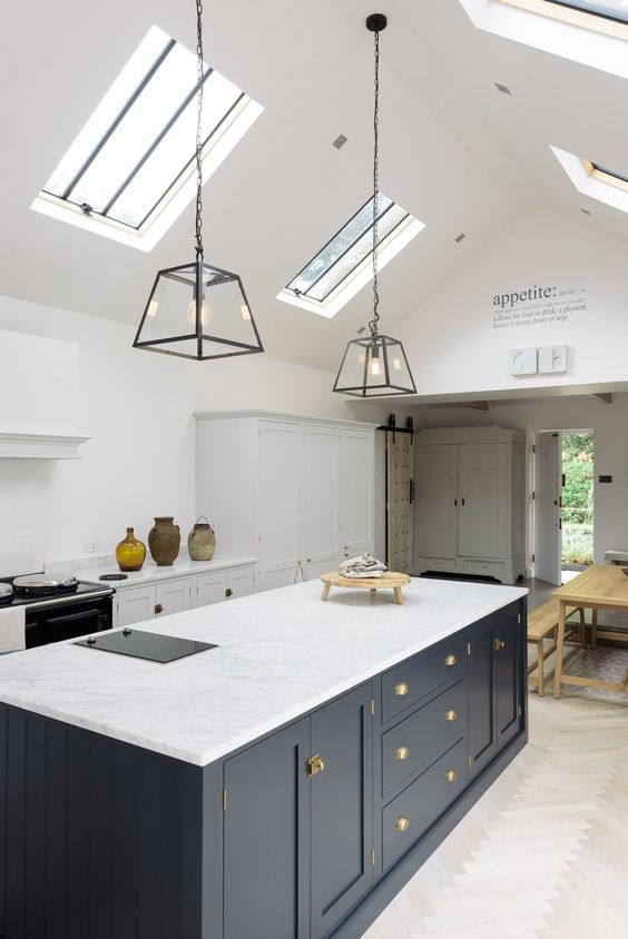 a stylish kitchen in white with a Victorian feel and a navy ktichen island, skylights and pendant lamps highlight the space