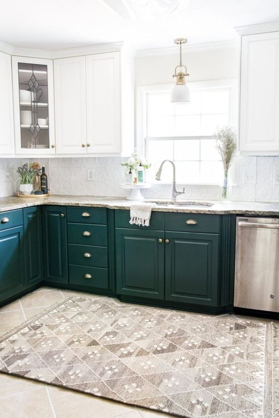 a stylish kitchen with dark green and white cabinets, stone countertops and touches of metallics here and there