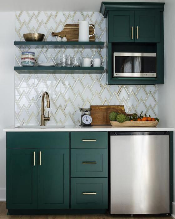 a stylish kitchen with hunter green cabinets, a zig-zag tile backplash and touches of gold for a chic look