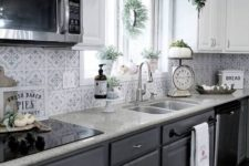 a stylish kitchen with white upper cabinets, graphite grey lower ones, a mosaic tile backsplash and stone countertops
