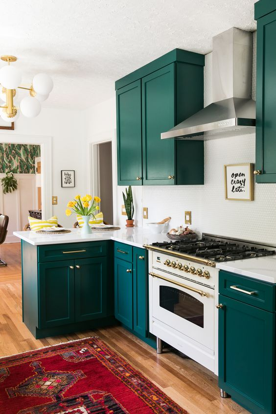 a super bold kitchen with teal cabinets, a white penny tile backsplash and countertops plus gold touches here and there