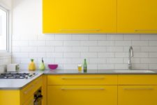 a super bright contemporary kitchen with yellow cabinets, a white subway tile backsplash and a wooden floor looks wow