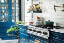 a super brigth blue kitchen with a white tile backsplash and lots of gold for pulling off art deco style