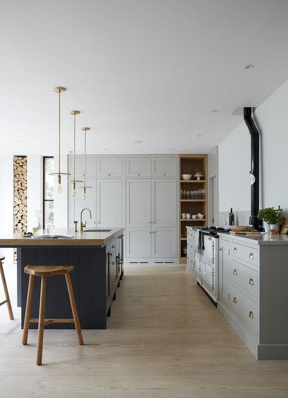 a traditional dove grey kitchen, a navy kitchen island with a wooden countertop and wooden stools to match it