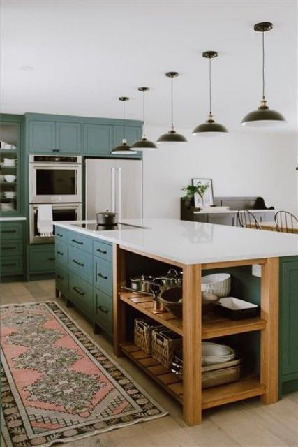 a traditional kitchen done in green, with white countertops, black lamps and a boho rug for a chic look