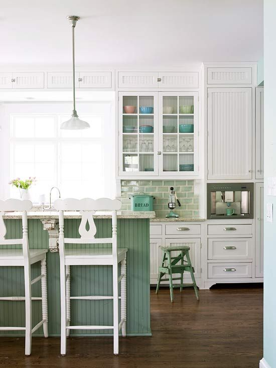 a traditional kitchen done with white cabinets and furniture, with a green kitchen island and tile backsplash for a touch of color