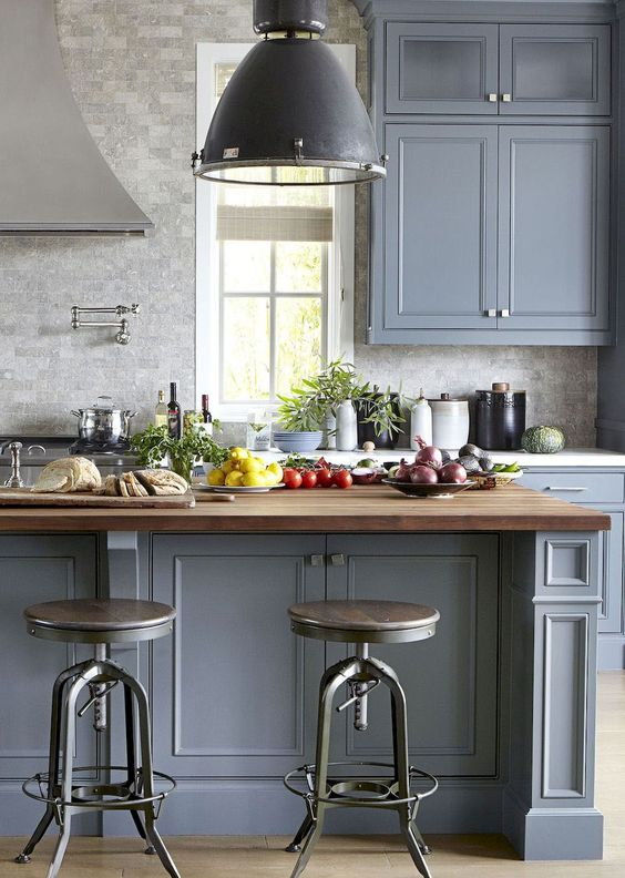 a traditional kitchen in slate blue with a grey tile, butcherblock countertops and vintage furniture and lamps