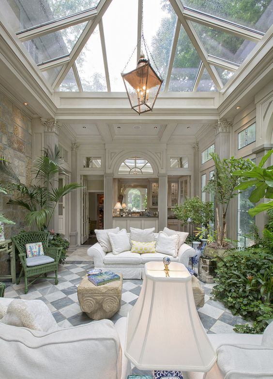 a traditional space done in a biophilic way, with lots of potted plants and a glass ceiling for much natural light and views