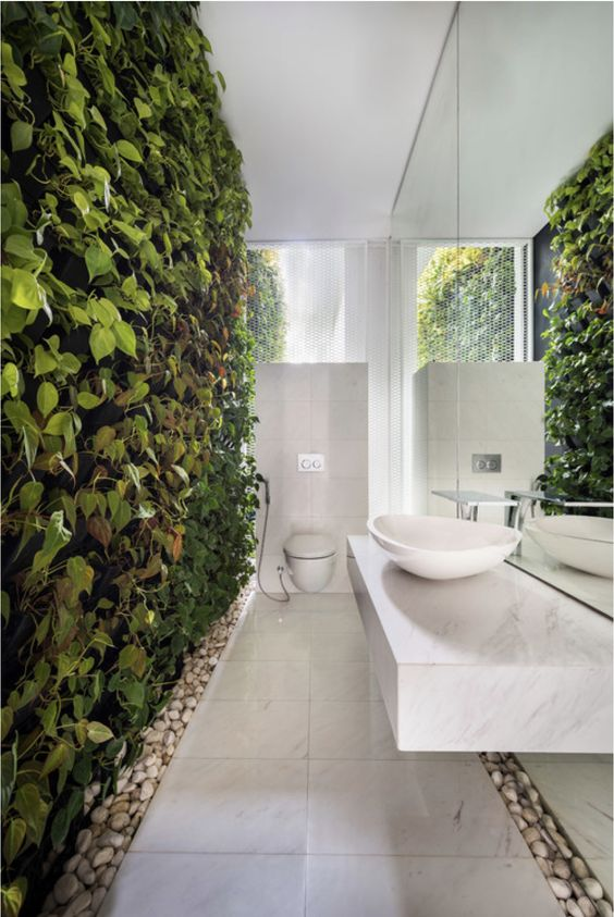 a truly biophilic bathroom done in neutrals and with a living wall and pebbles on the floor for a natural touch
