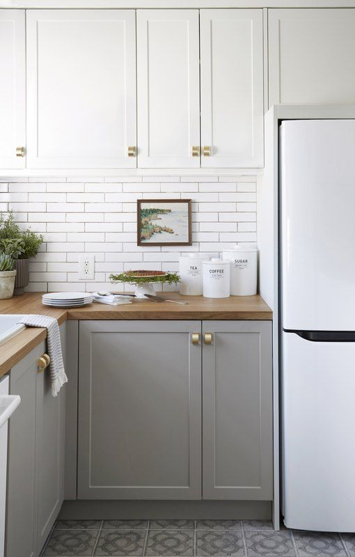 a two tone kitchen with white upper cabinets, dove grey lower ones, wooden countertops and gold handles