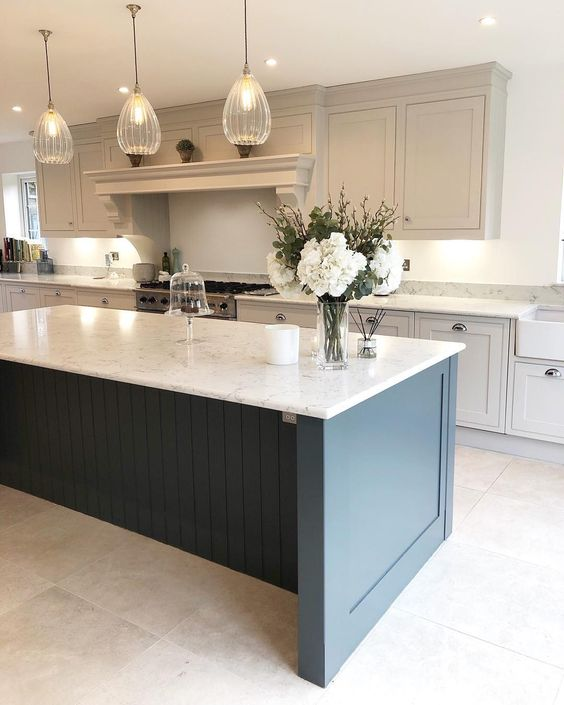 a vintage dove grey kitchen with a statement navy kitchen island and white sone countertops plus glass pendant laps