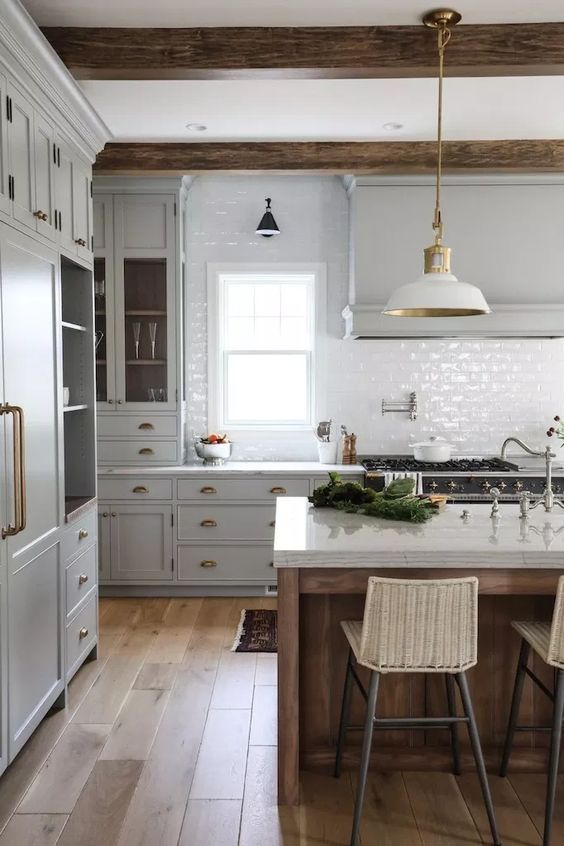 a vintage kitchen with dove grey cabinets, white tile backsplash, white lamps and wooden beams plus a kitchen island