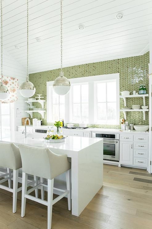 a welcoming kitchen with white cabinets, a white stone kitchen island, a green tile wall and touches of metallic shades