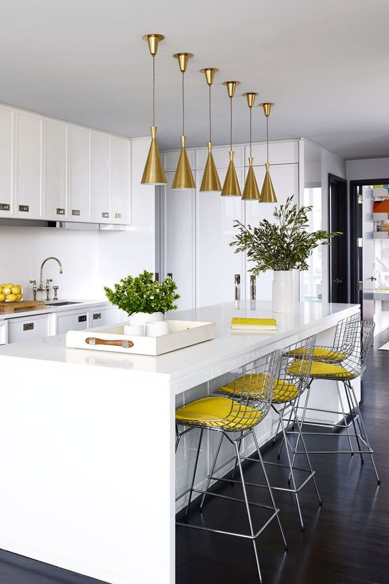a white kitchen done with slight yellow accents   yellow stools and lemons in a bowl plus gold lamps over the island