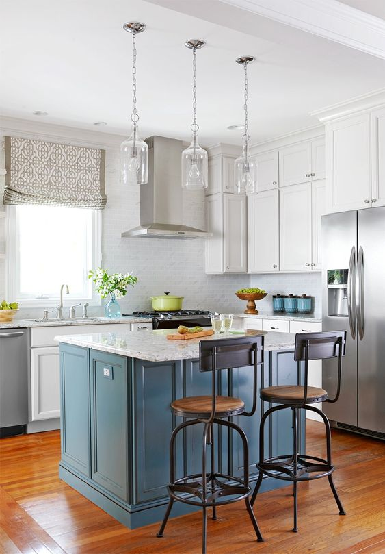 a white kitchen with a grey tile backsplash and a blue kitchen island plus white stone countertops is chic