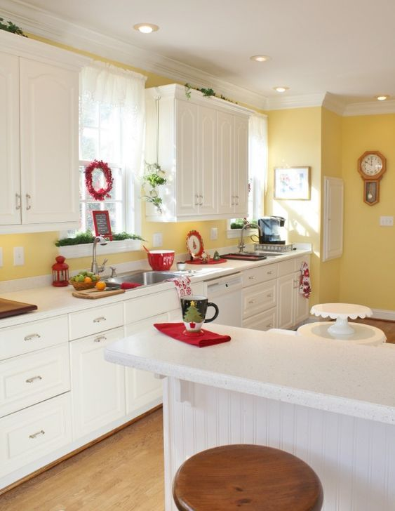 a white vintage kitchen with a sunny yellow backsplash and accent wall, touches of red and fresh greenery