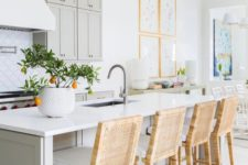 an airy kitchen with dove grey cabinets and a kitchen island, white stone countertops, wicker stools and frame chandeliers
