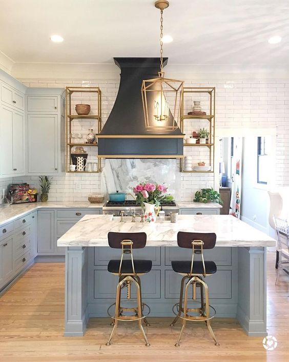 an art deco kitchen with powder blue cabinets and a kitchen island completed with a white stone countertop and a tile backsplash