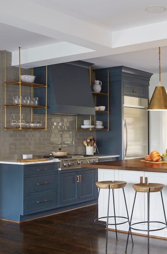 an elegant vintage blue kitchen with a grey subway tile backsplash and touches of gold and natural wood here and there