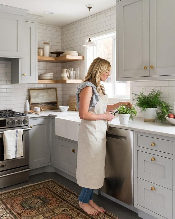 dove grey cabinets, a white tile backsplash and white countertops, wooden shelves and a boho rug for a chic look