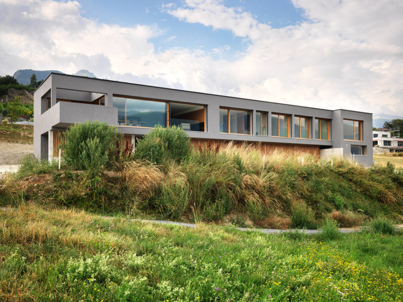 This beautiful linear house is called ROFR, it's built of concrete on Swiss slopes and the seismic activity was considered while building the house