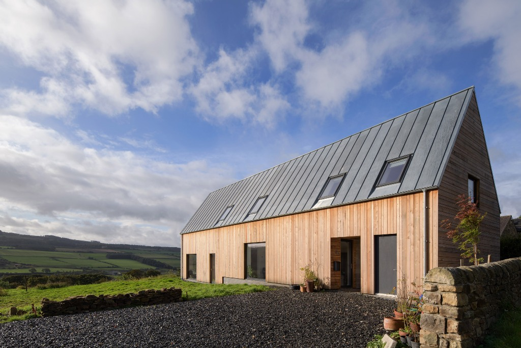 This beautiful modern house is built barn like and looks cozy, chic and very inviting perfectly blending with the landscape
