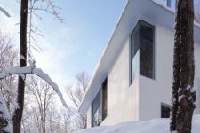 02 The house is clad with white wood and there are windows dotting the whole facade to let more light in
