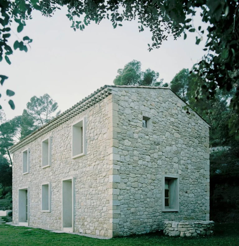 The house resembles a stone barn, there are many windows to bring light in and glazed doors