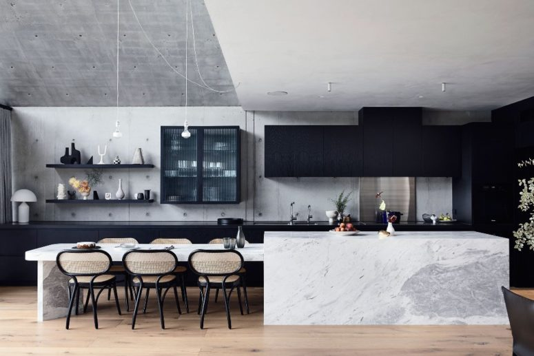 The kitchen is done with sleek black cabinets, a white marble kitchen island and chic chairs