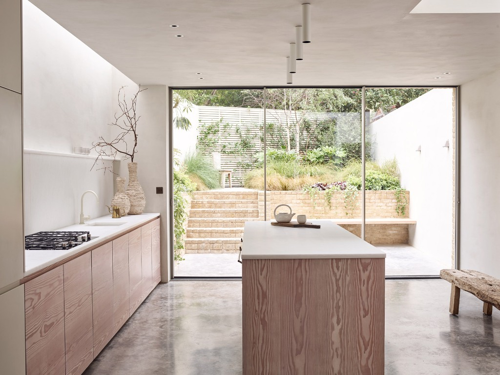 The kitchen is peaceful and neutral, the cabinets are only lower ones, lots of white surfaces create a calm feel, and a glazed door brings much natural light